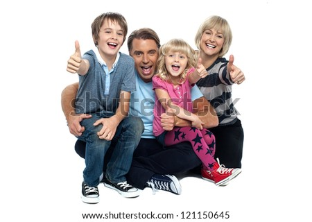 Happy thumbs up family of four sitting on studio floor. - stock photo