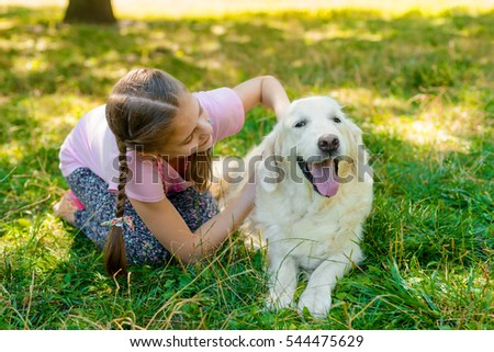 Happy time for a child who sits on the grass in the park near her favorite dog. Young girl caresses her pet and looks on golden retriever.