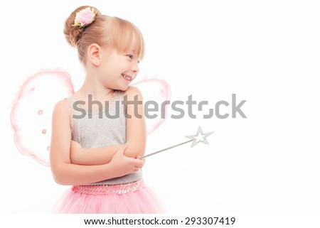 Happy time. Pleasant little fair-haired girl wearing fairy costume and holding hands in front of her while laughing. - stock photo