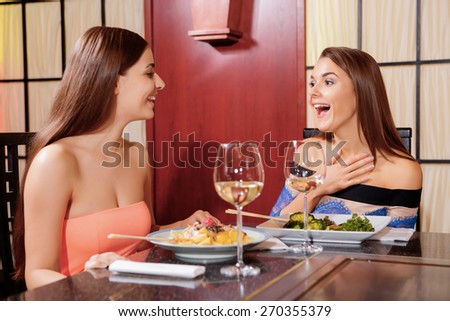 Happy time together. Two beautiful female friends happily laugh sitting in a Japanese restaurant - stock photo