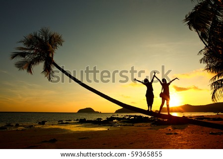 happy time, two girl stand on coconut tree on the beach with sunset time , Thailand, Asia - stock photo