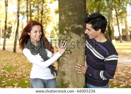 Happy times between a young couple at the park in autumn season (selective focus with shallow DOF) - stock photo