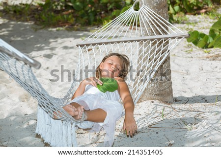 happy tired  little girl  lying and sleeping on hammock in tropical garden on sunny warm day - stock photo