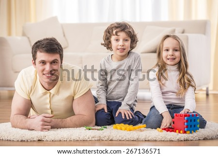 Happy to be a family. Father with kids playing in living room. - stock photo