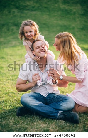 Happy to be a family.Happy family of three playing and laughing while sitting on grass outdoors - stock photo