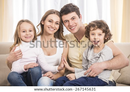 Happy to be a family. Portrait of happy family with kids on the couch. - stock photo