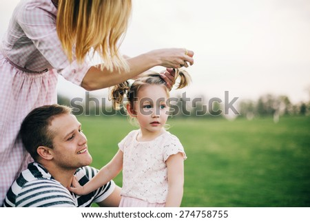 Happy to be a family.Young father smiles to his daughter while mother making her hair - stock photo