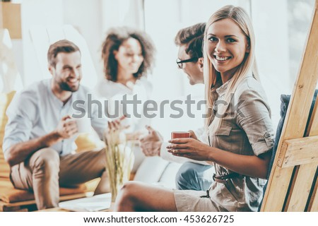 Happy to be a part of a great team. Happy young woman holding cup of coffee and looking at camera while her colleagues discussing something in the background