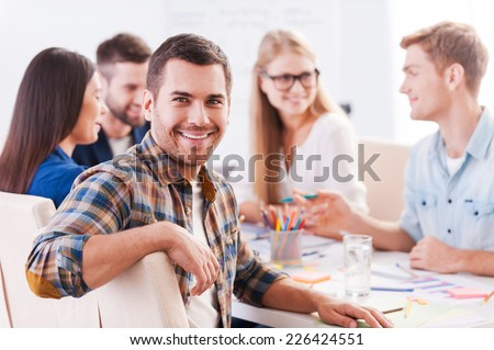 Happy to be a part of creative team. Group of cheerful business people in smart casual wear sitting together at the table and discussing something while handsome man looking at camera and smiling  - stock photo