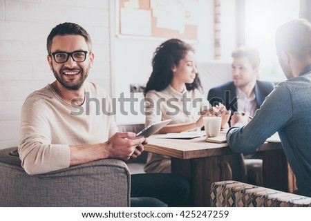 Happy to be a part of great team. Cheerful young handsome man looking at camera with smile while sitting at the office table on business meeting with his coworkers - stock photo
