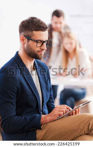 Happy to be a part of team. Confident young woman holding digital tablet and smiling while man standing in the background and pointing whiteboard  - stock photo