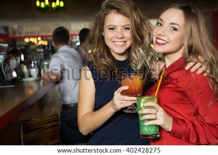 Happy to be friends. Two fabulous females smiling magnetically and holding drinks at the local bar.