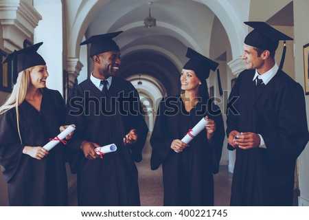 Happy to be graduated. Four college graduates in graduation gowns walking along university corridor and talking