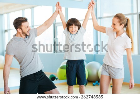 Happy to be healthy. Happy father and mother having fun with their son in health club with fitness balls laying in the background  - stock photo