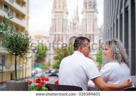 Happy to be together. Attractive elderly family couple sitting in sidewalk cafe. - stock photo
