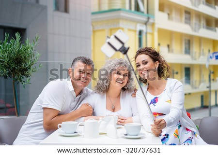 Happy to be together. Attractive elderly family couple with adult daughter taking selfie on smartphone in side walk cafe. - stock photo