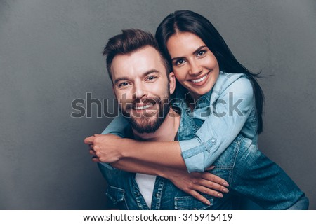 Happy to be together. Handsome young man piggybacking beautiful woman and smiling while standing against grey background - stock photo