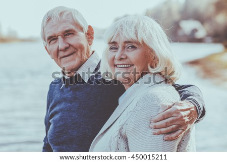 Happy to be together. Happy senior couple bonding to each other and smiling while standing on the quayside together - stock photo