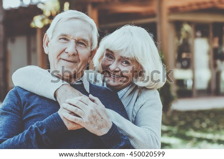 Happy to be together. Happy senior couple bonding to each other and smiling while standing outdoors and in front of their house - stock photo