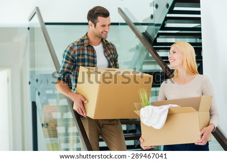 Happy to do everything together. Happy young couple holding cardboard boxes while going down the stairs  - stock photo