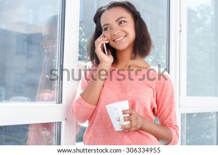 Happy to hear you. Portrait of young attractive smiling mulatto girl standing on background of window, holding cup and talking per mobile phone. - stock photo