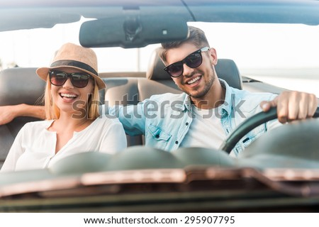 Happy to travel together. Joyful young couple smiling while riding in their convertible  - stock photo