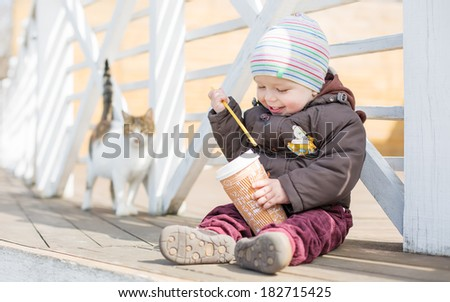 happy toddler baby boy sitting by the fence and holds a glassful - stock photo
