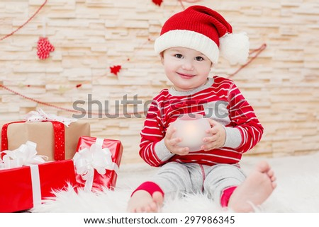 Happy toddler baby Santa holding a candle - stock photo