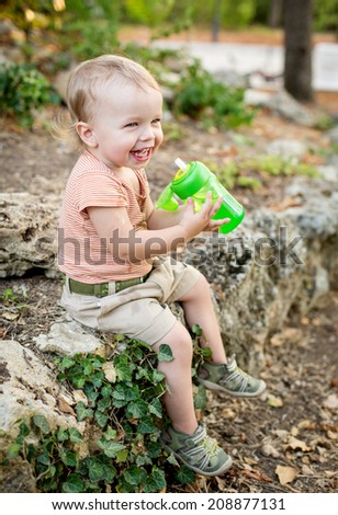 happy toddler boy drinks water sitting - stock photo