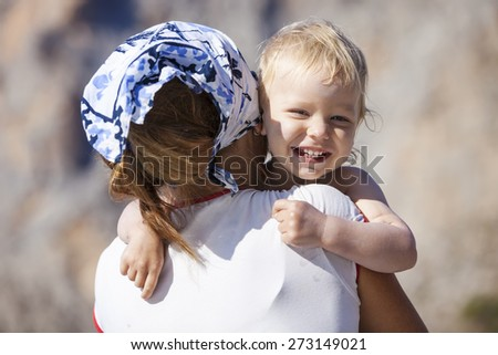 Happy toddler boy embracing mother and laughing - stock photo