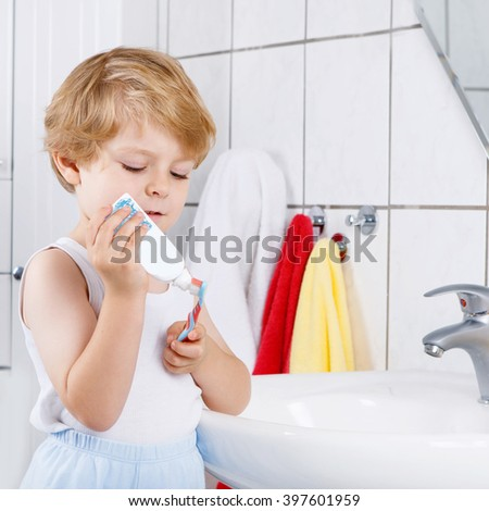 Happy toddler boy learning brushing his teeth in domestic bath. Children learning how to stay healthy. - stock photo