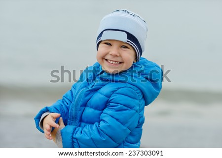 happy toddler boy outdoors wearing blue jacket - stock photo
