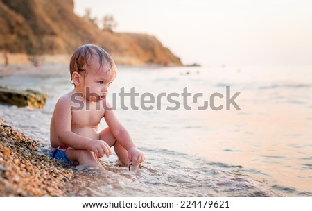 Happy toddler boy playing on the sea at sunset - stock photo