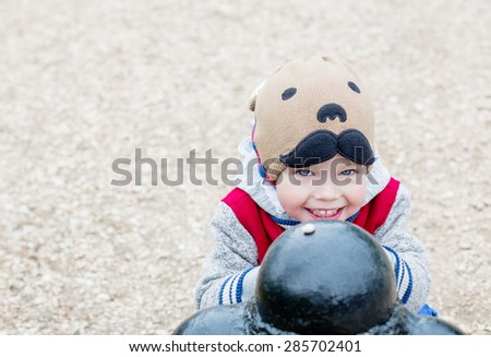 Happy Toddler boy playing outdoors on a beige background - stock photo