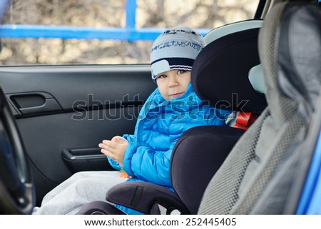 happy toddler boy sitting in the car seat - stock photo