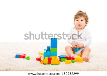 Happy toddler boy sitting on fur carpet and playing with bricks blocks isolated on white background