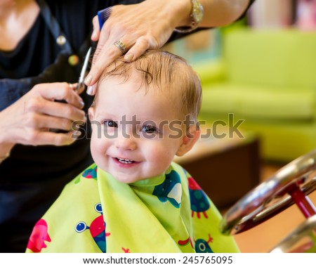 Happy toddler child getting his first haircut - stock photo