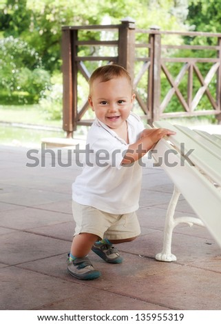 Happy toddler child leaning against a bench in a spring park or a patio garden, trying to get up, learning to walk.