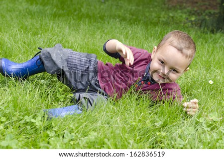 Happy toddler child playing and rolling in grass in garden or meadow. - stock photo