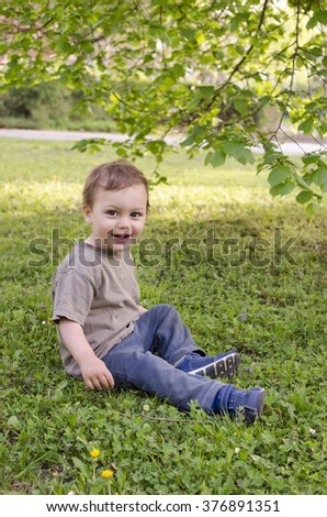 Happy toddler child sitting on grass under a tree in a park.