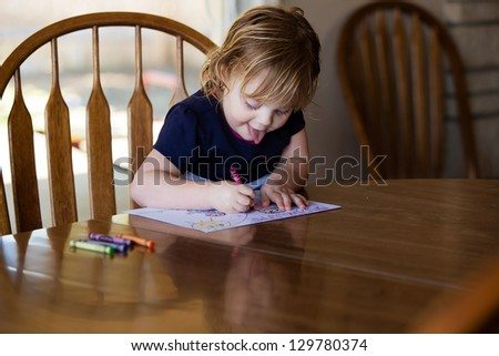 Happy toddler concentrating on coloring