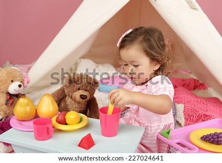 Happy toddler girl engaged in pretend play tea party indoors at home with a teepee tent