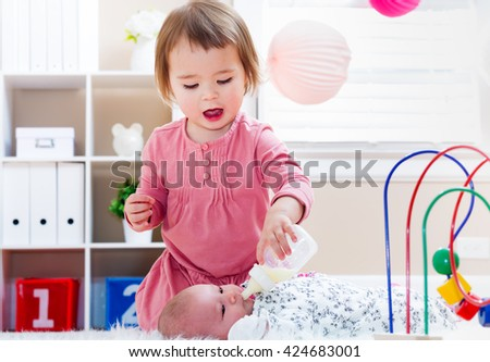 Happy toddler girl feeding her newborn baby sister a bottle - stock photo