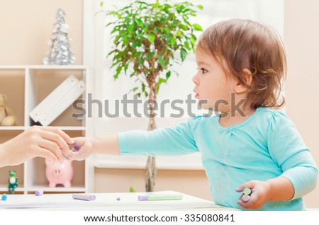 Happy toddler girl handing chalk to an adult inside her house - stock photo
