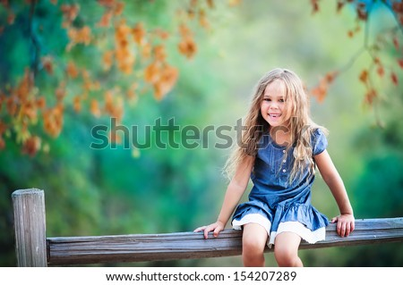 happy toddler girl has a fun and laughing at beautiful autumn park background - stock photo
