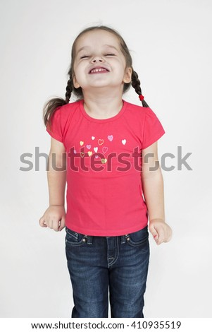 Happy toddler girl  having a great time and laughing.  Isolated on grey. - stock photo