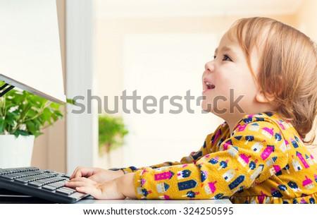 Happy toddler girl having fun using her computer - stock photo