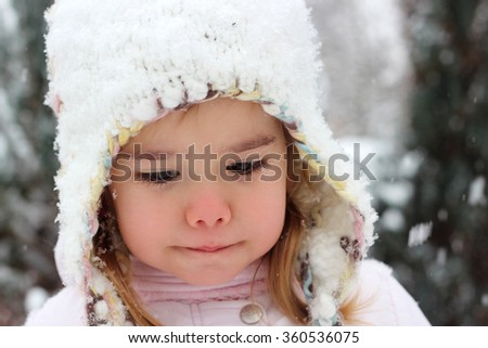 Happy toddler girl in warm coat and knitted hat dreaming in the winter forest, outdoor portrait, winter family concept