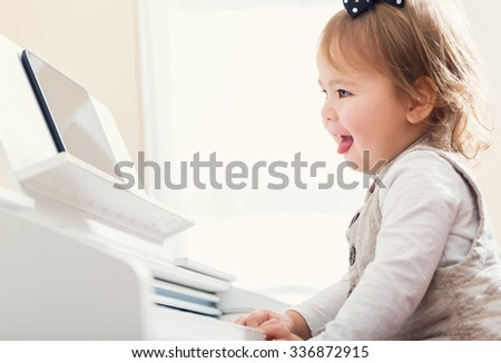 Happy toddler girl laughing and playing the piano while reading sheet music from her tablet - stock photo