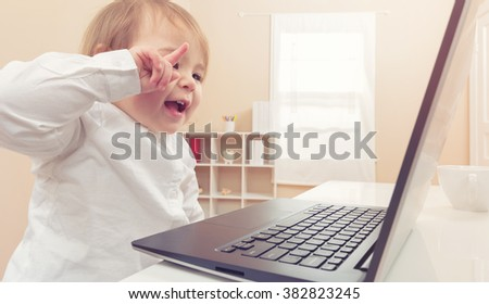Happy toddler girl laughing while using her laptop in her house - stock photo